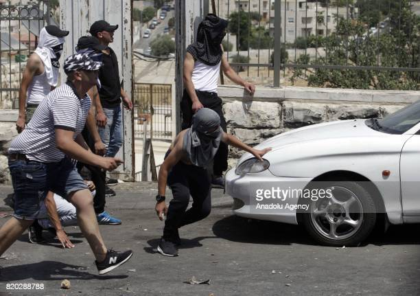 Palestinians response Israeli security forces' tear gas attack by throwing stones during a demonstration to protest metal detectors installed by...