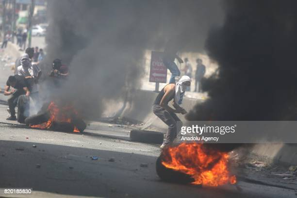 Palestinians response Israeli security forces' tear gas attack by throwing stones and burning tyres during a demonstration to protest Israeli...