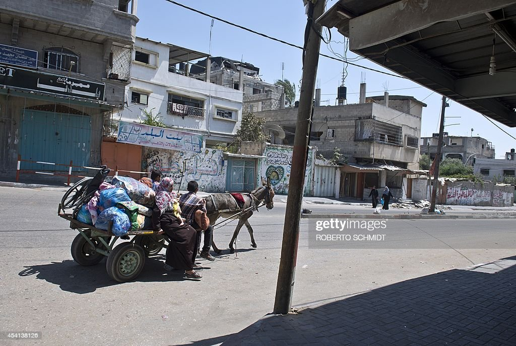 Palestinians ride a donkey pulled cart as they carry some of their belongings in a street of Beit Lahia on August 25, 2014. A quarter of Gaza's population of 1.8 million have been made homeless by the fighting between Hamas militants and Israel since July 8. Egyptian mediators have proposed a new ceasefire in Gaza that would open the blockaded enclave's crossings and allow in aid and reconstruction materials, a senior Palestinian official said.