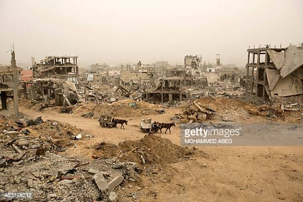 Palestinians ride donkey carts during a sandstorm on February 11 2015 next to buildings destroyed during last year's 50day war between Israel and...
