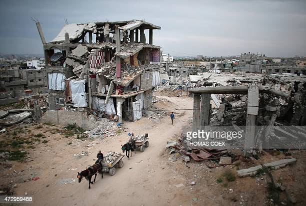 Palestinians ride their donkeycarts in the middle of rubble and destroyed buildings on May 11 in the Eastern Gaza City Shujaiya neighbourhood which...
