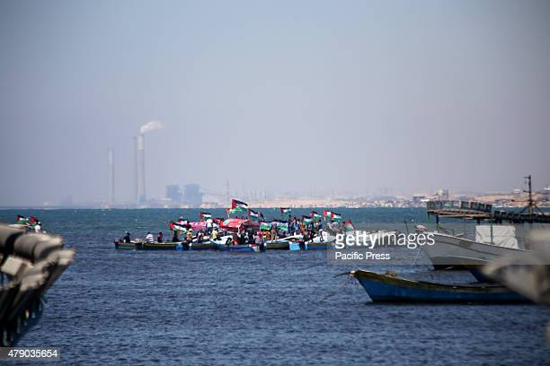 Palestinians riding boats hold Palestinian flags during a protest against the Israeli blocking of a boat of foreign activists from reaching Gaza at...