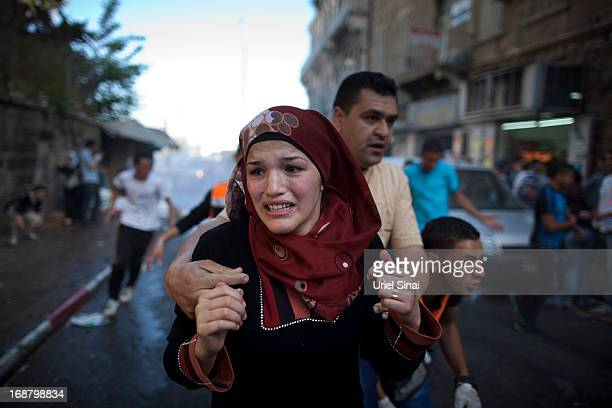 Palestinians run for cover during clashes between Palestinian demonstrators and Israeli police during a rally marking Nakba day on May 15 2013 out...