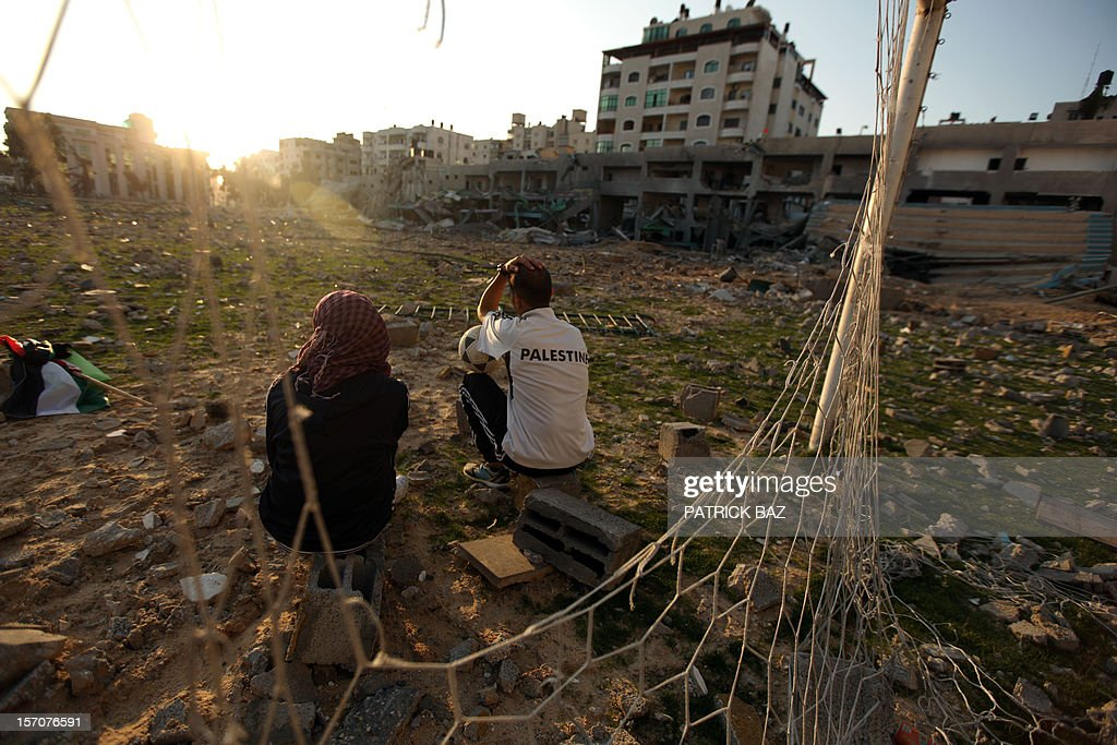 Palestinians, runner and football player Bilal Abu Samaan (R), 20, and athlet Ala Ayoub, 22, sit in the rubble of the bombed Palestine Stadium in Gaza City on November 28, 2012. The stadium was bombed by the Israeli airforce during a conflict between the ruling Hamas party and the Israeli military between 14 and 21 November 2012.