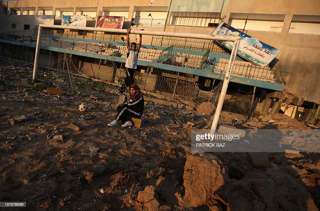 Palestinians, runner and football player Bilal Abu Samaan (back), 20, and female athlete Ala Ayoub, 22, pose in the rubble of the bombed Palestine Stadium in Gaza City on November 28, 2012. The stadium was bombed by the Israeli airforce during a conflict between the ruling Hamas party and the Israeli military between 14 and 21 November 2012.