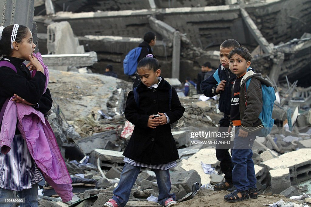 Palestinians school children are seen standing on the rubble of a destroyed building close to their school, hit during last week's Israeli offensive, in Gaza City, on November 24, 2012, three days after a truce was declared between Israel and Hamas. Gaza's children, virtually absent from the streets since the violence, are beginning to return to school after a truce between Israel and Gaza's Hamas rulers ended eight days of deadly bombardment.