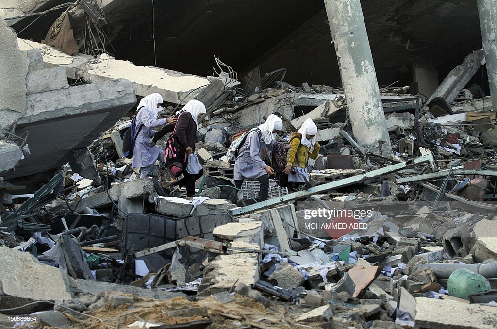 Palestinians school girls walk on the rubble of a building destroyed during earlier Israeli bombardment, as they make their way to their nearby school in Gaza City, on November 24, 2012, three days after a truce was declared between Israel and Hamas. Gaza's children, virtually absent from the streets since the violence, are beginning to return to school after a truce between Israel and Gaza's Hamas rulers ended eight days of deadly bombardment.