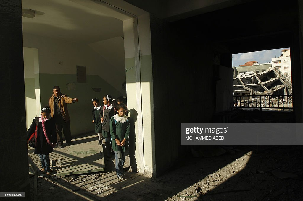 Palestinians school girls walks along a corridor of their school, damaged during last week's Israeli offensive, in Gaza City, on November 24, 2012, three days after a truce was declared between Israel and Hamas. Gaza's children, virtually absent from the streets since the violence, are beginning to return to school after a truce between Israel and Gaza's Hamas rulers ended eight days of deadly bombardment. AFP PHOTO/MOHAMMED ABED