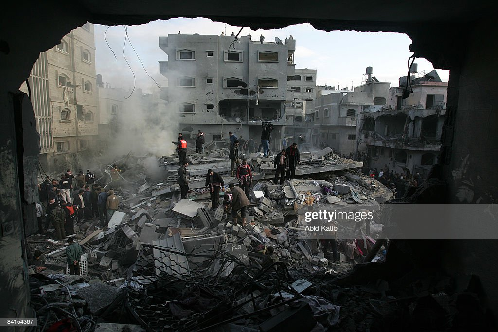 Palestinians search for bodies in the rubble of the destroyed house of Hamas senior leader Nizar Rayan after an Israeli missiles strike, in the refugee camp of Jabaliyaon January 1, 2009 in Gaza, Gaza Strip. Israeli warplanes attacked government buildings in the Gaza Strip on New Year's Day after Israel and its Islamist Hamas foe both spurned ceasefire calls in a conflict that has killed around 400 Palestinians and injured around 1,600.