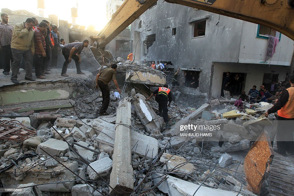 Palestinians search through the debris of the destroyed home of the al-Dallu family following an Israeli air strike in Gaza City, on November 18, 2012. At least seven members of the same family, including four children, were among nine people killed when an Israeli missile struck a family home in Gaza City, the health ministry said.