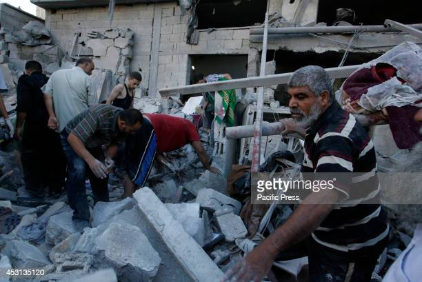 Palestinians search through the rubble for survivors following an Israeli air strike that killed nine members of alGhul family in Rafah in the...