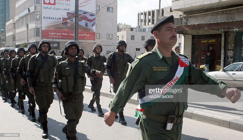 Palestinians security forces march along the streets of the West Bank city of Hebron, on Januray 1, 2013, as they mark the 48th anniversary of the formation on the Fatah movement. The Fatah anniversary commemorates the first operation against Israel claimed by its armed wing then known as Al-Assifa (The Thunderstorm in Arabic) on January 1, 1965. AFP PHOTO / HAZEM BADER
