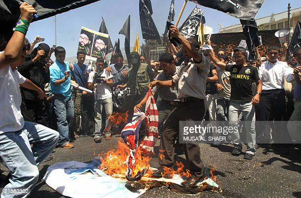 Palestinians set fire to a US flag during a demonstration in the West Bank city of Bethlehem 04 August 2006 against the Israeli ofensive in Lebanon...