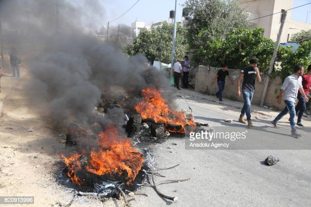 Palestinians set tyres on fire on the road as Israeli forces siege around the hometown of a Palestinian man Monir alAbed who allegedly killed three...