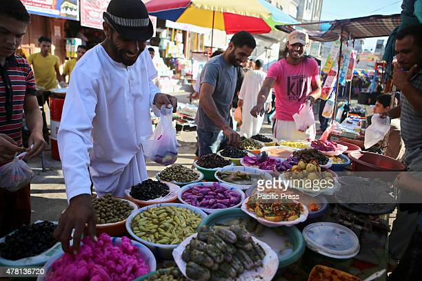 Palestinians shop in a street market on the fifth day of the holy month of Ramadan in Rafah in the southern Gaza Strip