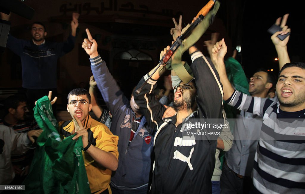 Palestinians shout and flash the V-sign for victory as they celebrate the beginning of the truce with Israel in Gaza City on November 21, 2012. Palestinians in Gaza took to the streets to celebrate the start of a truce deal with Israel that was announced in Egypt on the eighth day of violence in and around Gaza.