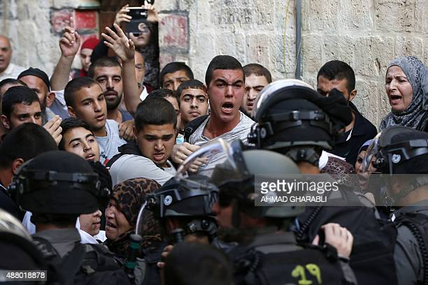 Palestinians shout in front of Israeli security forces who block a road leading to the AlAqsa mosque compound in Jerusalem's Old City on September 13...
