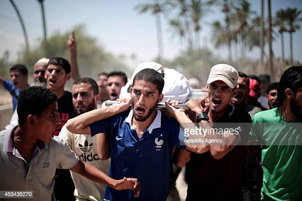 Palestinians shout slogans and carry the body of a Palestinian boy named Ahmed alMisri killed by an Israeli assault targeted on an agricultural land...