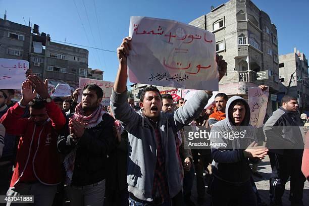 Palestinians shout slogans during a demonstration held to protest regular power cuts following the death of two children who had burnt to death from...