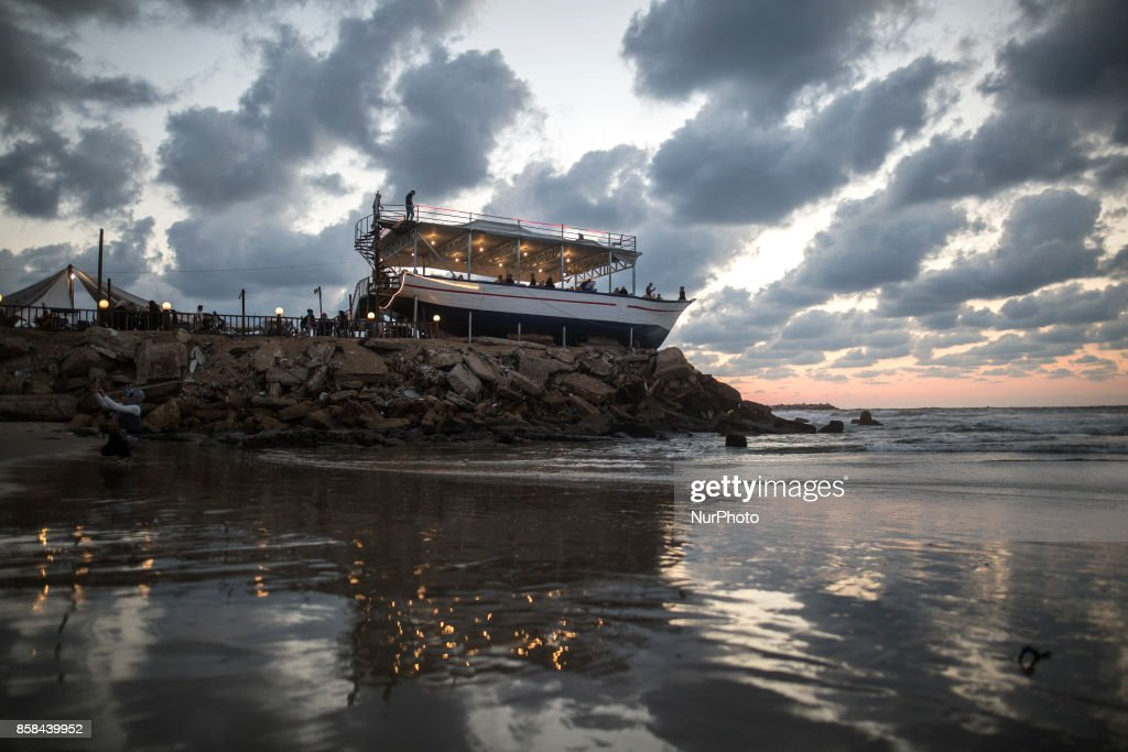 "Palestinians sit at ""Lolo Rose"" ship which a popular cafe in front of beach in Gaza City during sunset, on October 6, 2017."