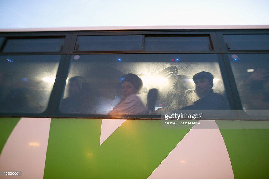 Palestinians sit in a bus as a new line is made available by Israel to take Palestinian labourers from the Israeli army crossing Eyal, near the West Bank town of Qalqilya, into the Israeli city Tel Aviv, on March 4, 2013.Thousands of Palestinians enter Israel to work every day after receiving permits, many of them in private vans. The new line will not be available for Jewish settlers.