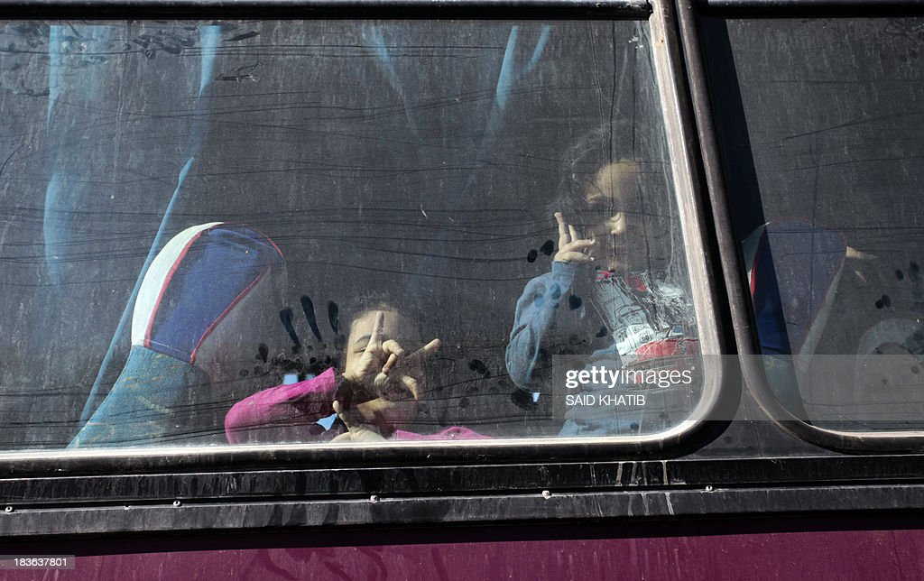 Palestinians sit in a coach as they wait to cross into Egypt at the Rafah crossing terminal in the southern Gaza Strip on the border with Egypt on October 8, 2013. Hundreds of patients, students and foreign residents from the Palestinian side have rushed to the Rafah crossing after the Egyptian announcement of re-opening it for 5 days.
