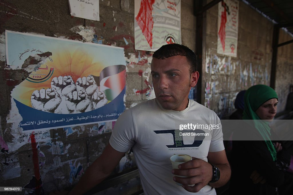 Palestinians sit in front of a wall covered with nationalist posters as they wait for their bus at the town's central station on April 6, 2010 in Jenin, West Bank. The Cinema Jenin team of German professionals, local Palestinian staff and foreign volunteers, with funding from the German government, the Roger Waters foundation and other sponsors, are tuning the city's run-down cinema into a modern cinematheque. Their stated aim is to encourage a culture of cinema-going for both the population of Jenin and its refugee camp, and to provide the city with a sustainable cultural centre while fostering principles of peaceful conflict resolution, co-existence and acceptance of others by denouncing all forms of violence and fanaticism.