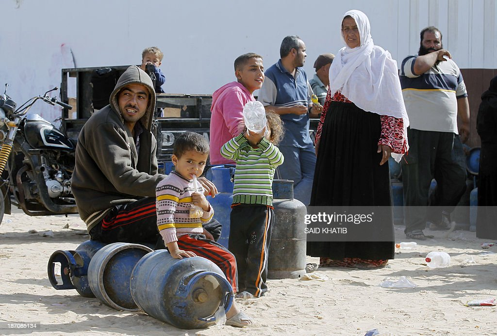 Palestinians sit on empty bottles as they queue to have their cooking gas bottles refilled in Rafah, in the southern Gaza Strip on November 6, 2013. Palestinian officials said Israel has limited the quantity of cooking gas entering into Gaza, which causes a shortage.