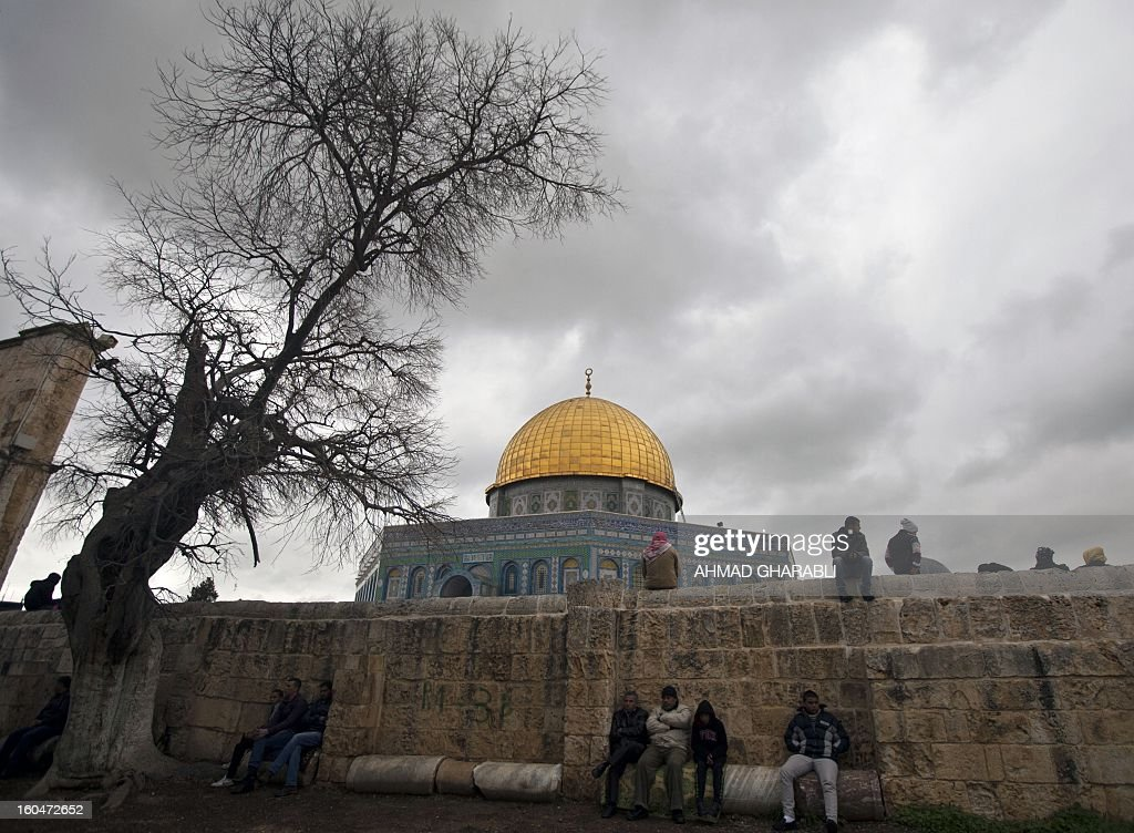 Palestinians sit outside the Dome of the Rock at the Al-Aqsa mosque compound in Jerusalem on February 1, 2013.