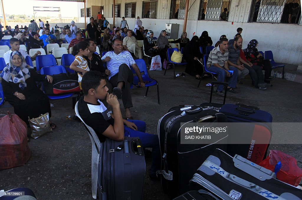 Palestinians sit with their luggage at the Rafah border terminal in the southern Gaza Strip as they wait to cross into neighbouring Egypt, on August 18, 2013, after the crossing was opened for humanitarian reasons and to allow medical patients through. The Egyptian authorities were set to re-open the Rafah border crossing with Gaza, to allow entry to the territory, the Hamas government which rules the Gaza Strip said. AFP PHOTO/ SAID KHATIB