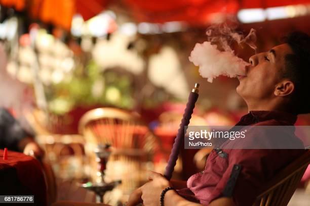 Palestinians smoke shisha or hookah at a coffee shop in Gaza City on May 11 2017