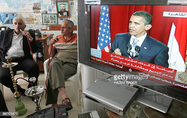 Palestinians smoke waterpipes as they listen to US President Barack Obama's speech at Cairo University at a shop in the West Bank city of Hebron on...
