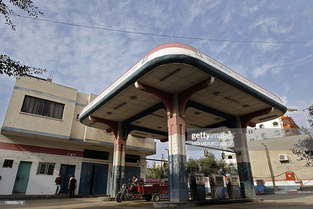 Palestinians stand at a petrol station which closed due to fear of Israeli bombardment in the village of Beit Lahia in the northern Gaza Strip on November 17, 2012. Israeli air strikes in Gaza killed 10 Palestinians on November 17, five of them militants, as nine Israelis were hurt by rocket fire, four of them soldiers, medics said.