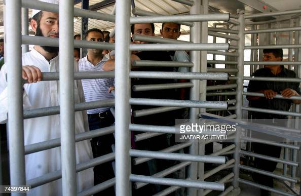 Palestinians stand at a turnstile during rally at the Hawara Israeli manned Israeli checkpoint to mark the 40th anniversary of the outbreak of the...