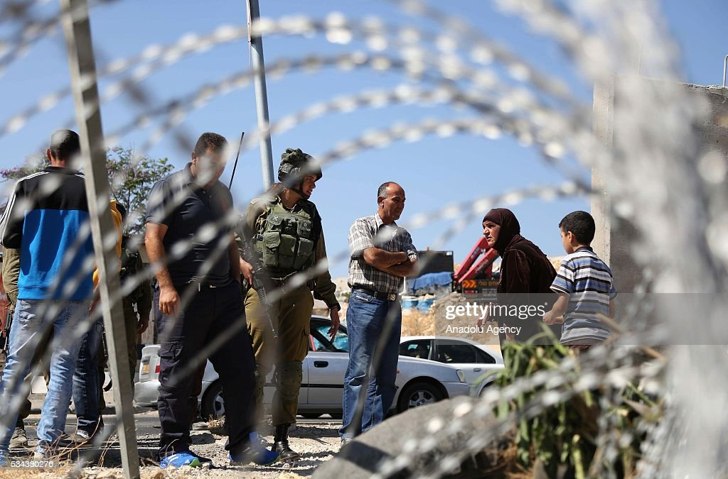 Palestinians stand behind the wire fence as Israeli security forces increase the security measures around Hizma district of Jerusalem on May 26, 2016.