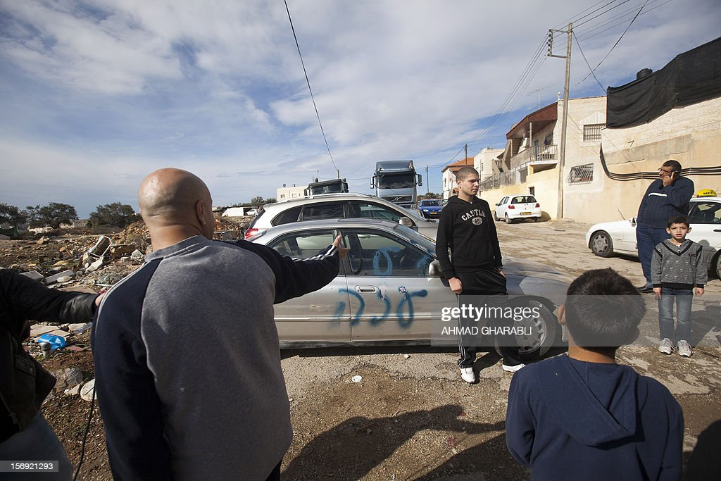 Palestinians stand next to a car with a graffiti reading in Hebrew 'Gaza: the price to pay' in the Palestinian neighborhood of Shuafat in Israeli annexed East Jerusalem, , on November 25, 2012. Unknown assailants vandalized 8 cars belonging to Palestinians, apparently in retaliation for the recent events in Gaza, the police said today. AFP PHOTO / AHMAD GHARABLI