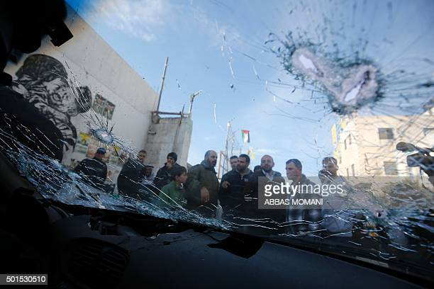 Palestinians stand next to two cars used by Palestinians in an attempted ramming attack against Israeli soldiers in the Qalandiya refugee camp near...