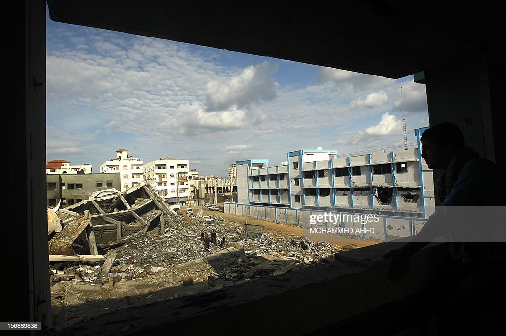 Palestinians stand on the rubble of a building destroyed during earlier Israeli bombardment adjacent to a United Nations run school (R), in Gaza City, on November 24, 2012, three days after a truce was declared between Israel and Hamas. Gaza's children, virtually absent from the streets since the violence, are beginning to return to school after a truce between Israel and Gaza's Hamas rulers ended eight days of deadly bombardment.