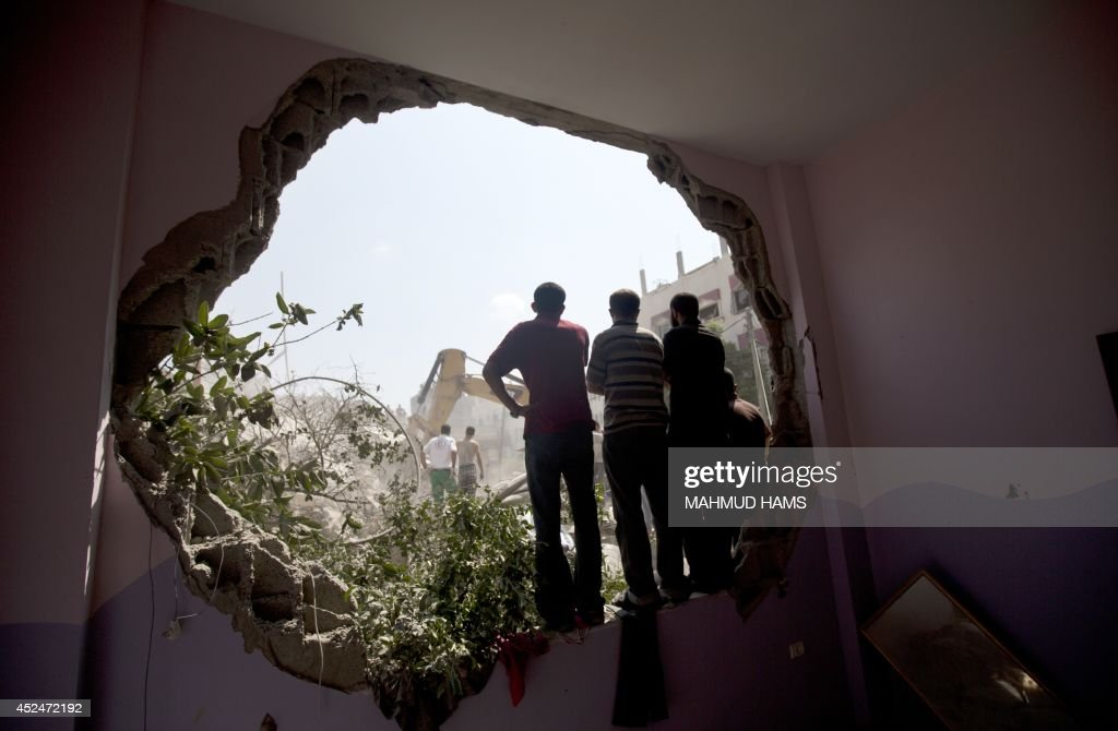 Palestinians stand watching from a hole in a wall as Civil Defence workers remove the rubble of a building destroyed in an Israeli air strike in Gaza...