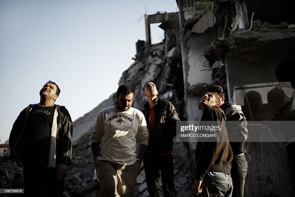 Palestinians stare at a house destroyed by an Israeli airstrike on Gaza City on November 20, 2012. Seven Palestinians were wounded in strikes on Gaza overnight, but no one was killed in the first night without fatalities since the Israeli air campaign began nearly a week ago. AFP PHOTO/MARCO LONGARI