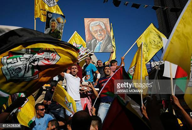 TOPSHOT Palestinians supporting the Fatah movement wave both their national and the movement's flags as they take part in a demonstration in the West...
