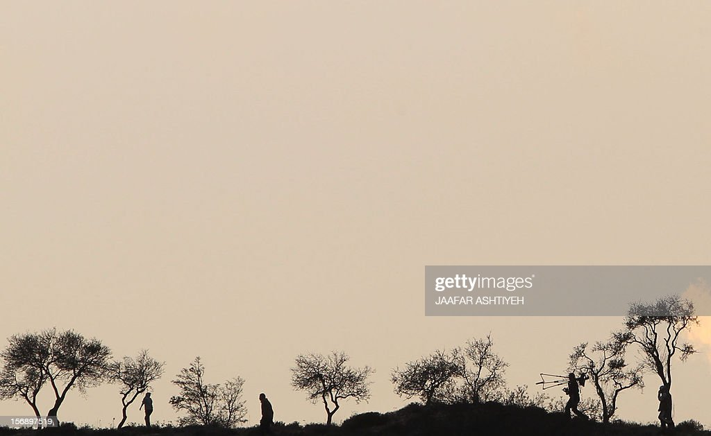 Palestinians take cover amongst trees during clashes with Israeli soldiers after Israeli settlers attacked villagers in the northern West Bank village of Qusra on November 24, 2012. PHOTO