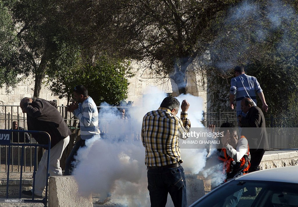 Palestinians take cover as a tear gas cannister explodes during clashes with Israeli security at a protest following the death of a Palestinian prisoner being held in an Israeli jail on April 2, 2013, at the entrance of Jerusalem's Old City next to the Damascus Gate. The Palestinian leadership blamed Israel for the death of Maisara Abu Hamdiyeh, a long-term prisoner with cancer, hiking tensions over a tinderbox issue closely followed on the Palestinian street.