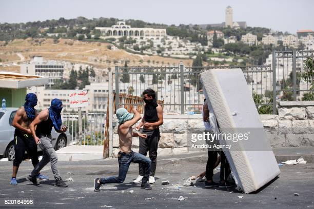 Palestinians take cover during a demonstration to protest metal detectors installed by Israeli authorities to AlAqsa Mosque Compund after performing...