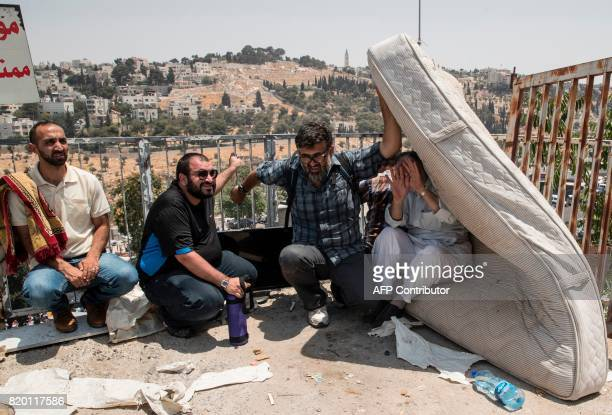 TOPSHOT Palestinians take cover during clashes between Palestinian worshippers and Israeli security forces outside Jerusalem's Old City following the...