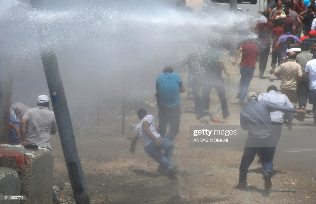 Palestinians take cover from a water cannon being fired by Israeli security forces during clashes at the Qalandia checkpoint between Ramallah and Jerusalem on July 1, 2016, as Israeli authorities banned men under 45 from accessing the Al-Aqsa mosque compound for Friday prayers. The Palestinian health ministry said that a middle-aged man had died from tear gas fired by Israeli forces during a clash at the Qalandia crossing. Israeli police said in a statement that three members of the security forces were injured by stones but it reported no Palestinian casualties. / AFP / ABBAS
