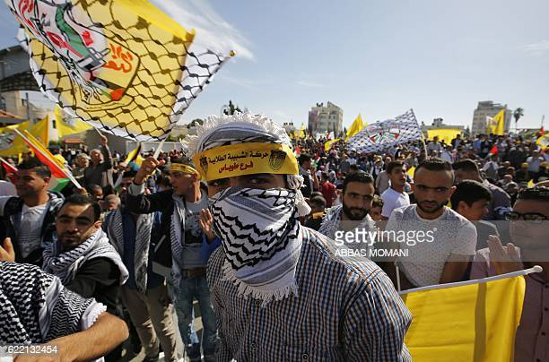 TOPSHOT Palestinians take part in a rally marking the 12th anniversary of the death of late Palestinian leader Yasser Arafat in the West Bank city of...