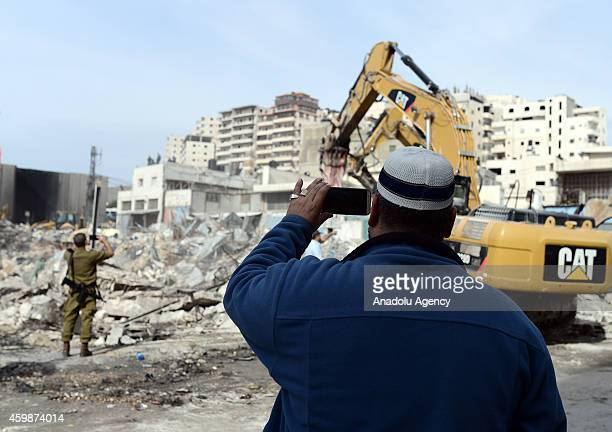 Palestinians take pictures of collapsed buildings after Israeli soldiers demolish Palestinians buildings and a market due to 'officially...