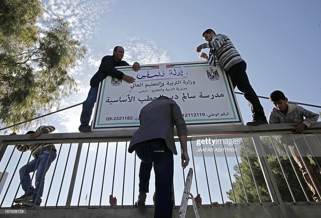 Palestinians teacher and students tape a banner reading 'State of Palestine' instead of 'Palestinian Authority' on a board at the entrance of the Salem Dair al Hatab school on December 2, 2012 in eastern Nablus, West Bank. Palestinian president is due home from New York to a hero's welcome today, after the United Nations voted to recognise Palestine as a non-member state. AFP PHOTO / JAAFAR ASHTIYEH
