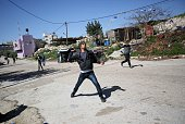A Palestinians throw a stone against Israeli security forces during clashes following a protest against closure of the village road in the West Bank...